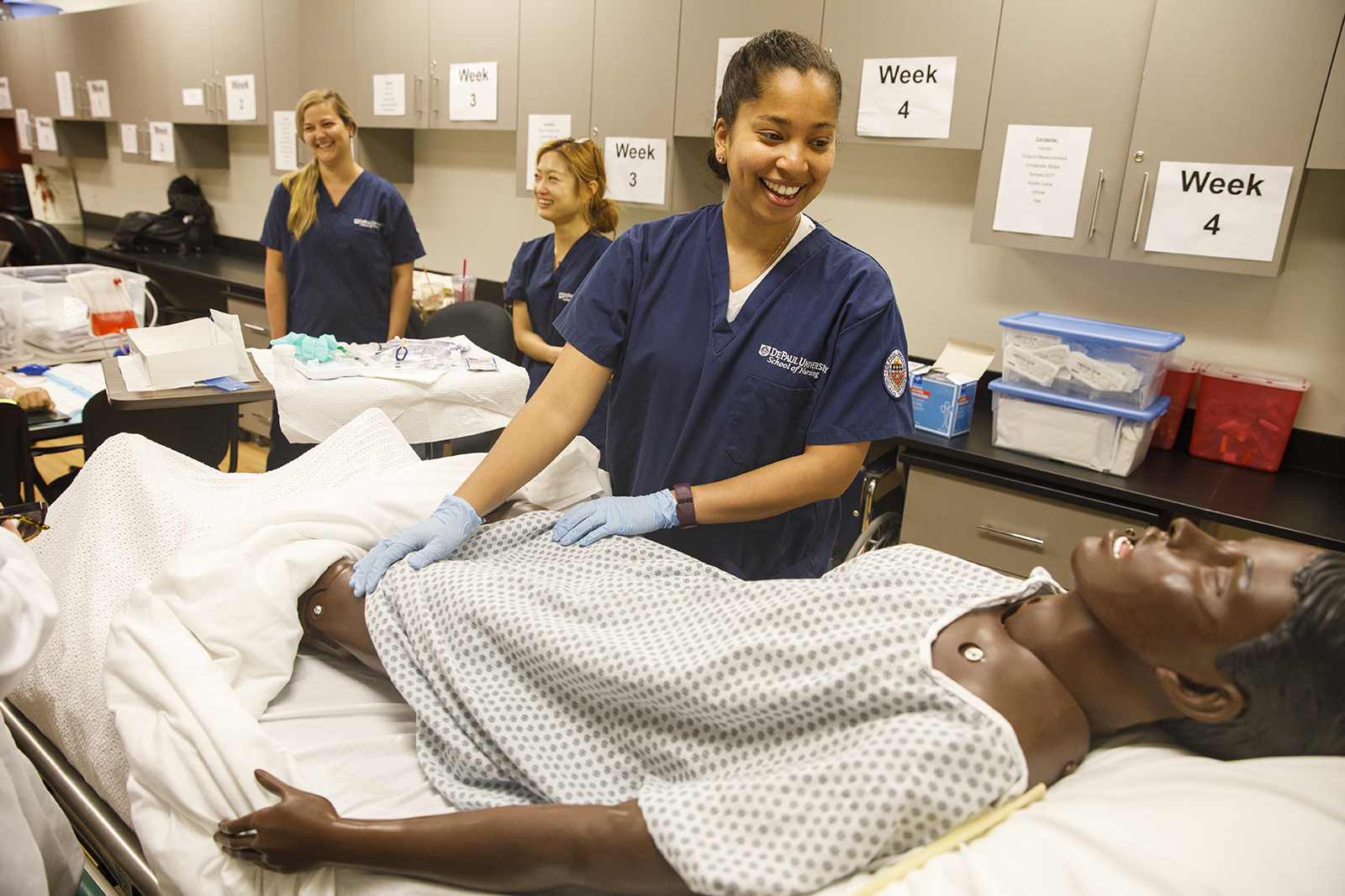 Stacy Gates, MENP student and veteran of the Army National Guard, prepares to assess a patient in the simulation lab.